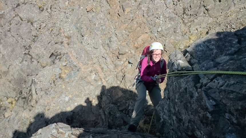 A happy client abseiling down the final difficulties of An Caisteal